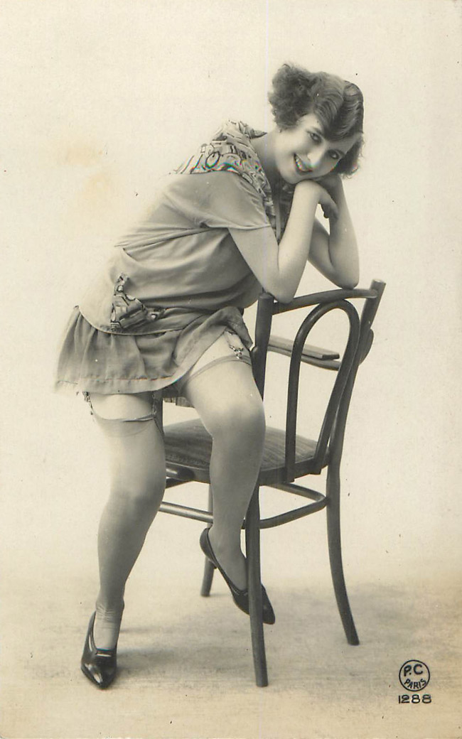 Lady sitting on arm of chair, leaning on the back - French Risqu