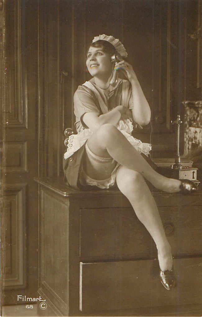 Lady sitting on the dresser, leg up, talking on phone