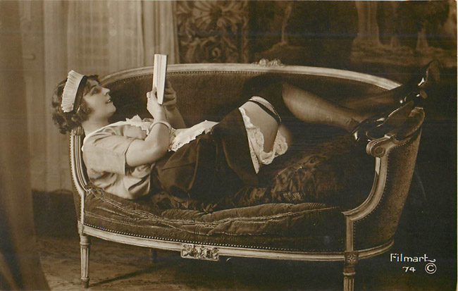 Lady laying on the couch, reading with legs up - French Risque