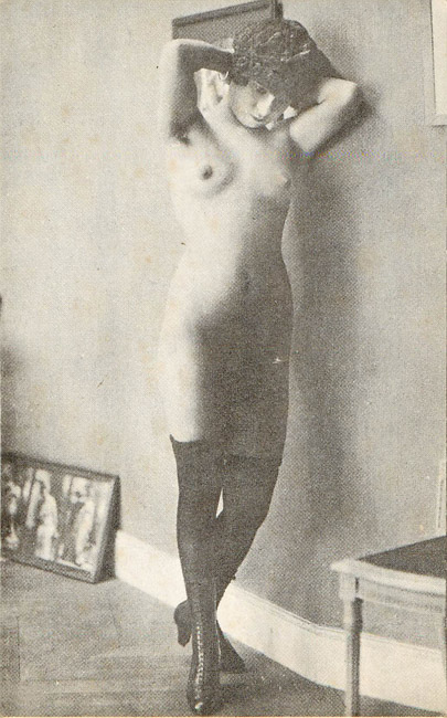 Woman standing against wall, nude with stockings and boots