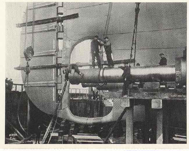 Workers fitting the Titanics propeller shafts into place. (1911)