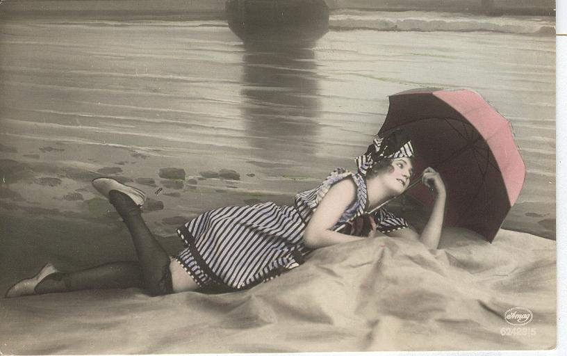 Woman laying on beach...wearing stockings, holding umbrella