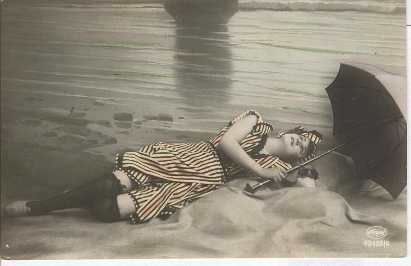 Woman gazing at the sky, wearing stockings, lying on the beach