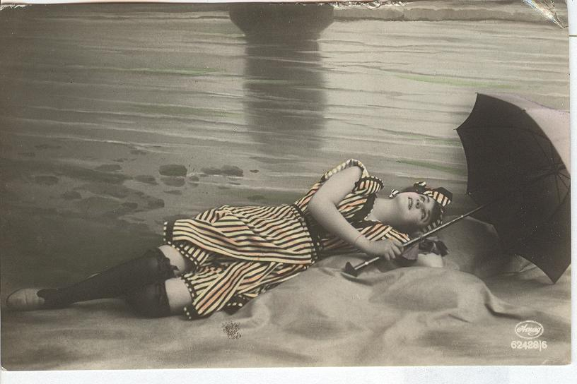 Woman in striped dress lying on beach w/umbrella...stockings